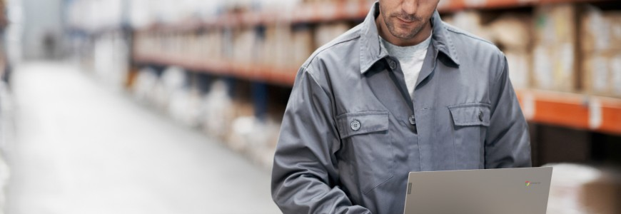 A young man using his notebook and checking his notes while working in a warehouse